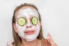 有自然奶油色面具的在她的面孔的妇女和黄瓜 免版税库存图片