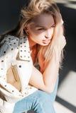 有自然构成与蓝眼睛和性感的嘴唇的俏丽的肉欲的年轻金发碧眼的女人在牛仔裤的一时兴的皮夹克坐 免版税库存图片