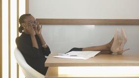 有自然构成的年轻可爱的美国黑人的妇女投入她的镜片,当坐与腿时 免版税图库摄影