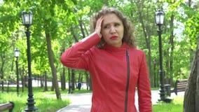 有自然构成的沮丧的女孩遭受头疼在公园 影视素材