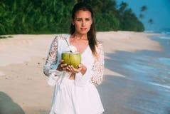 有自然构成的美丽的光亮的年轻深色的女孩沿海滨走,喝一个可口新鲜的椰子 免版税库存图片