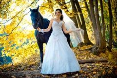 有自然构成的走与沿秋天的马的美丽的愉快的新娘和俏丽的微笑停放 免版税库存图片