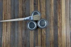 有自然油漆和油的在木backgro的瓶子和刷子 免版税库存照片