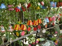 有自然环境的五颜六色的陶瓷风铃在有机兰花种田与小植物和动画片装饰 库存图片