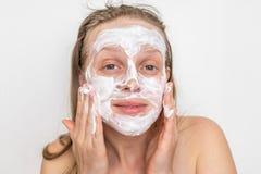 有自然白色奶油色面具的妇女在她的面孔 免版税库存照片