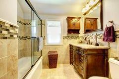 有自然石头和木头机柜的卫生间。 免版税库存图片