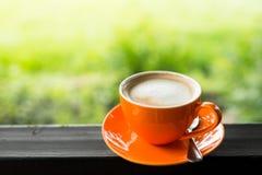 有自然bokeh的橙色咖啡杯 免版税库存照片