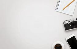 有自由空间的办公桌文本的 照相机,咖啡,巧妙的电话,笔记薄,在白色桌上的铅笔 库存照片