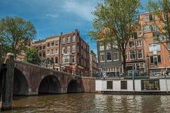 有自行车、被停泊的小船、老砖瓦房和晴朗的蓝天的桥梁在阿姆斯特丹 库存照片