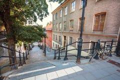 有自行车和台阶的老街道在历史房子之间在斯德哥尔摩,瑞典 库存照片