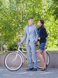 有自行车和女孩的一个人沿街道走 免版税图库摄影