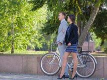 有自行车和女孩的一个人沿街道走 免版税库存图片