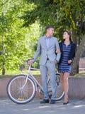 有自行车和女孩的一个人沿街道走 图库摄影