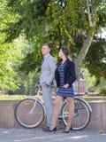 有自行车和女孩的一个人沿街道走 库存图片