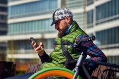 有自行车和智能手机的一个年轻人基于一条长凳在城市 免版税库存图片
