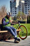 有自行车和智能手机的一个年轻人基于一条长凳在城市 库存照片
