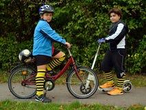 有自行车和滑行车的男孩 库存照片