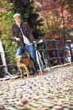有自行车和狗的年轻人 免版税库存照片
