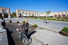 有自行车步行的前辈通过与历史大厦的阿訇正方形 免版税库存照片