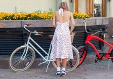 有自行车的一个少妇在明亮的葡萄酒衣物准备好节日减速火箭的巡航 库存照片