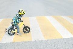 有自行车的一个男孩横渡与黄色标号的一条行人交叉路 免版税库存照片