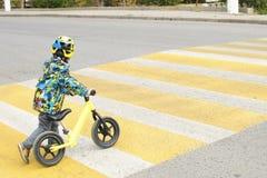 有自行车的一个男孩横渡与黄色标号的一条行人交叉路 库存照片