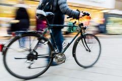 有自行车的人在行动迷离的购物街道上 库存照片