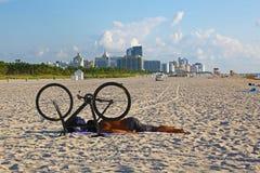 有自行车的人睡觉在海滩的 库存照片