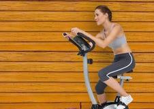 有自行车的健身妇女有黄色木背景 免版税库存照片