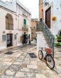有自行车的典型的白色街道在奥斯图尼,意大利 免版税库存图片