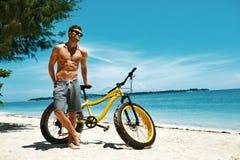 有自行车的太阳英俊的人晒黑在海滩的 katya krasnodar夏天领土假期 免版税库存图片