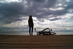 有自行车的女孩在海滩 免版税库存图片