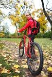 有自行车的女孩骑自行车者在自行车步行在秋天公园 库存图片