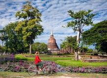 有自行车的妇女在寺庙附近在泰国 免版税库存照片