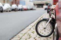 有自行车的孩子在穿过街道的停放的汽车之间 免版税库存图片