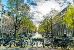 有自行车的小安静的运河在前面的桥梁在阿姆斯特丹的中心 免版税库存照片