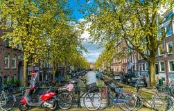 有自行车的小安静的运河在前面的桥梁在阿姆斯特丹的中心 免版税库存图片