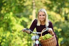有自行车的少妇在绿色公园 免版税库存图片