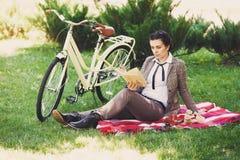有自行车的少妇有野餐在公园 库存照片