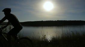 有自行车的年轻人在日落 股票录像