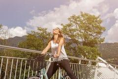 有自行车的年轻可爱的妇女在桥梁 免版税库存照片