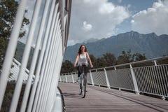 有自行车的年轻可爱的妇女在桥梁 图库摄影