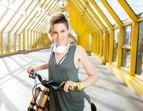 有自行车的年轻微笑的妇女在行人交叉路 库存图片