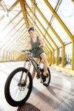 有自行车的年轻微笑的妇女在行人交叉路 免版税图库摄影