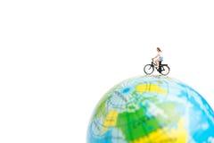 有自行车的微型人旅客在地球 免版税库存图片