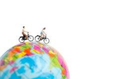 有自行车的微型人旅客在地球 免版税图库摄影