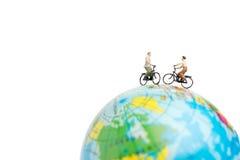 有自行车的微型人旅客在地球 库存照片