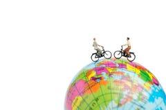 有自行车的微型人旅客在地球 图库摄影