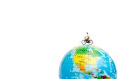有自行车的微型人旅客在地球 库存图片