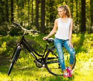 有自行车的微笑的十几岁的女孩在公园 库存图片